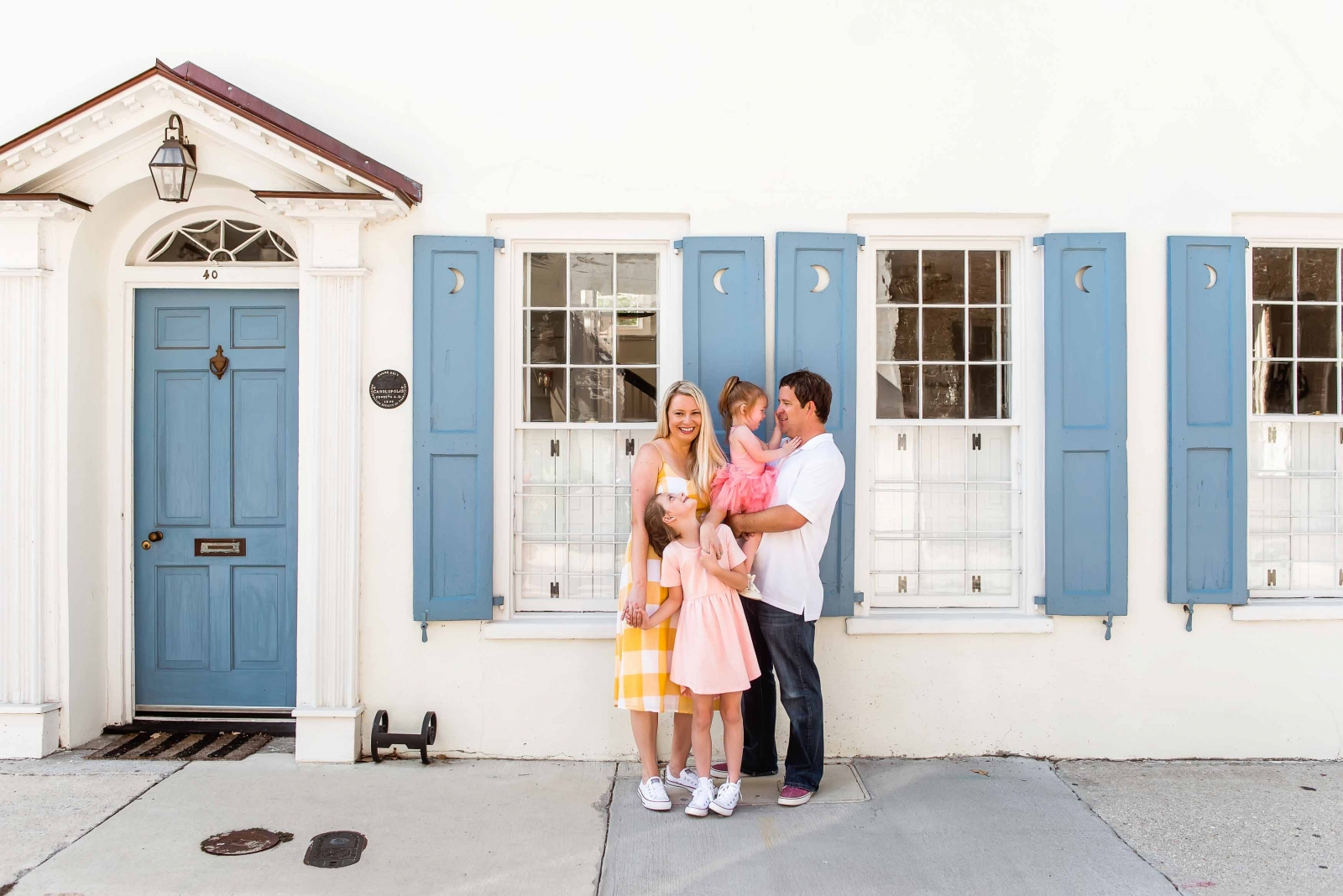 family hugging in front of colorful home in Charleston SC