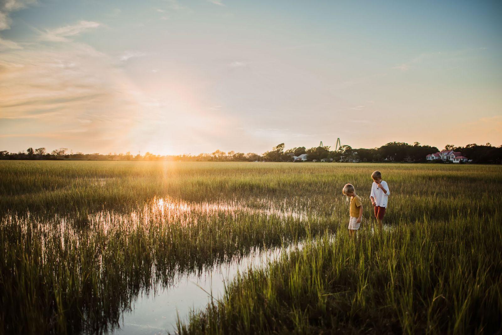 sunset landscape with two boys in SC salt marsh