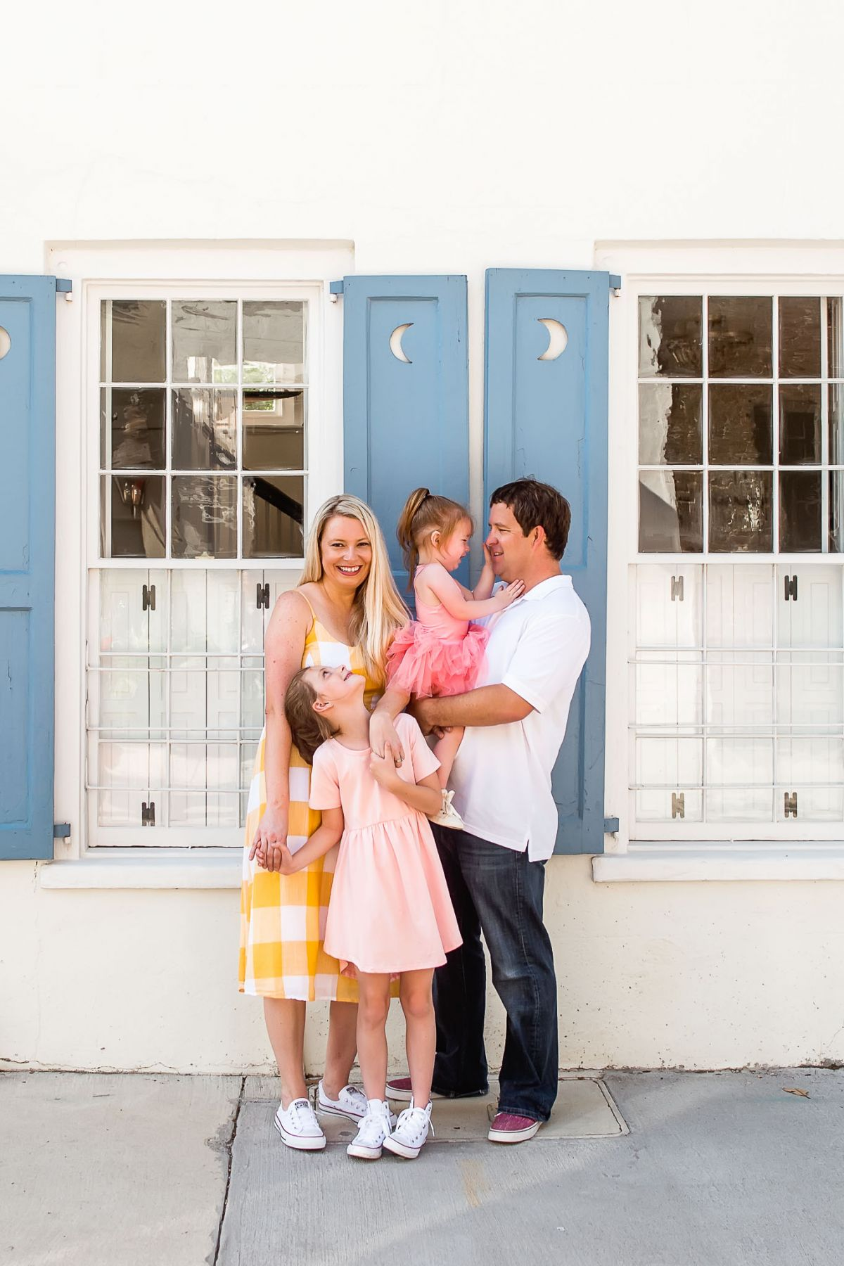 portrait of family hugging in front of colorful Charleston home