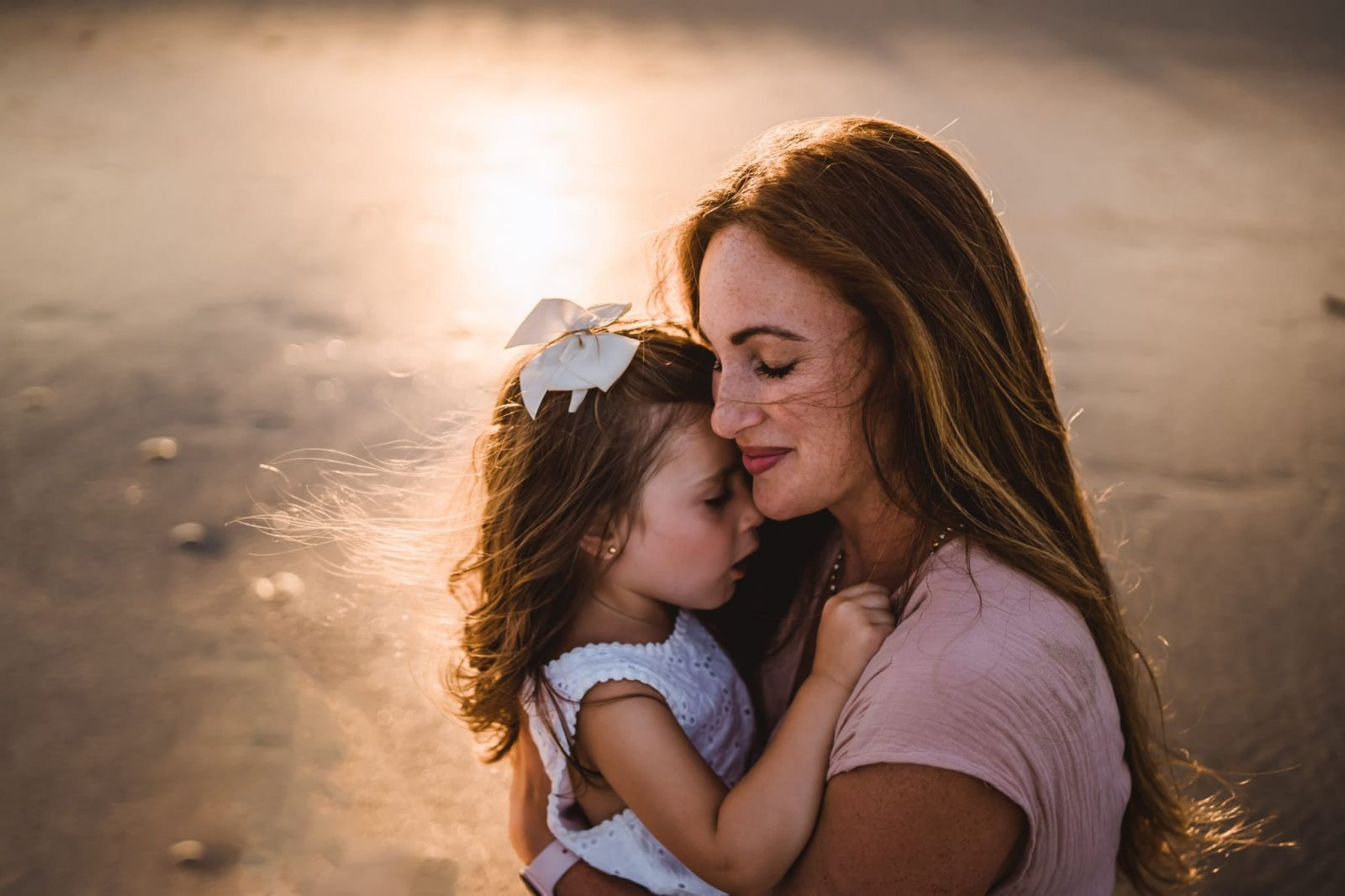Mom cuddling daughter in golden hour beach light
